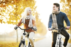 Beautiful couple rides bikes on a beautiful autumn day.