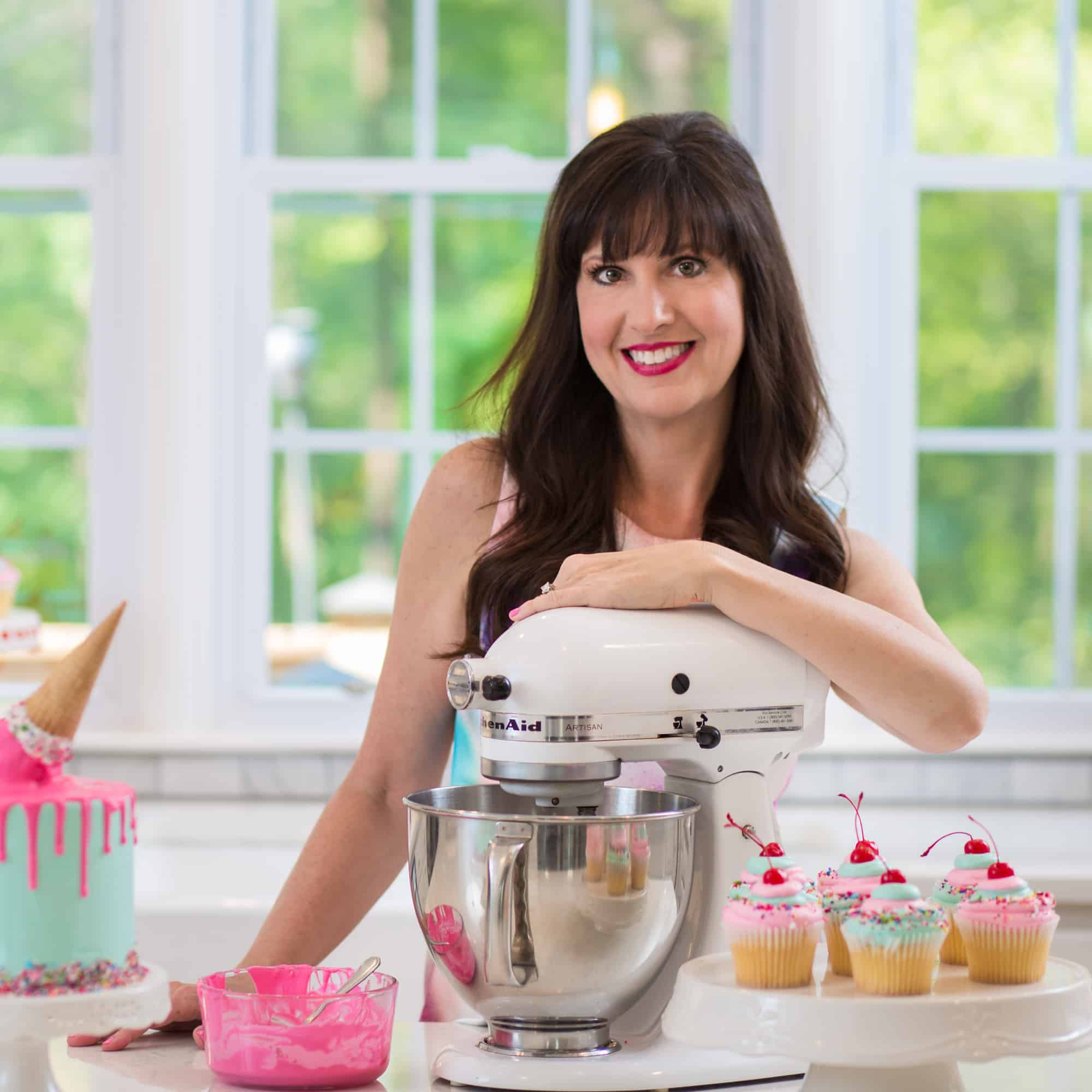 Lise Ode of Mom Loves Baking in her kitchen with baked goodies